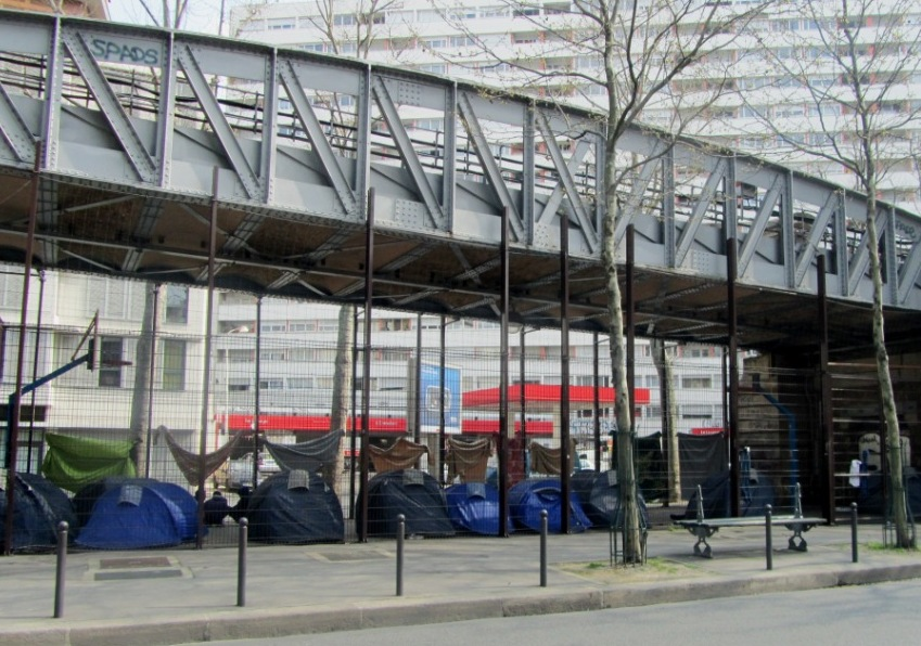 """Homeless people's tents under a metro train bridge in Paris"""